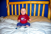 Ten month old James sitting on the bed at Uncle Bruce's house.